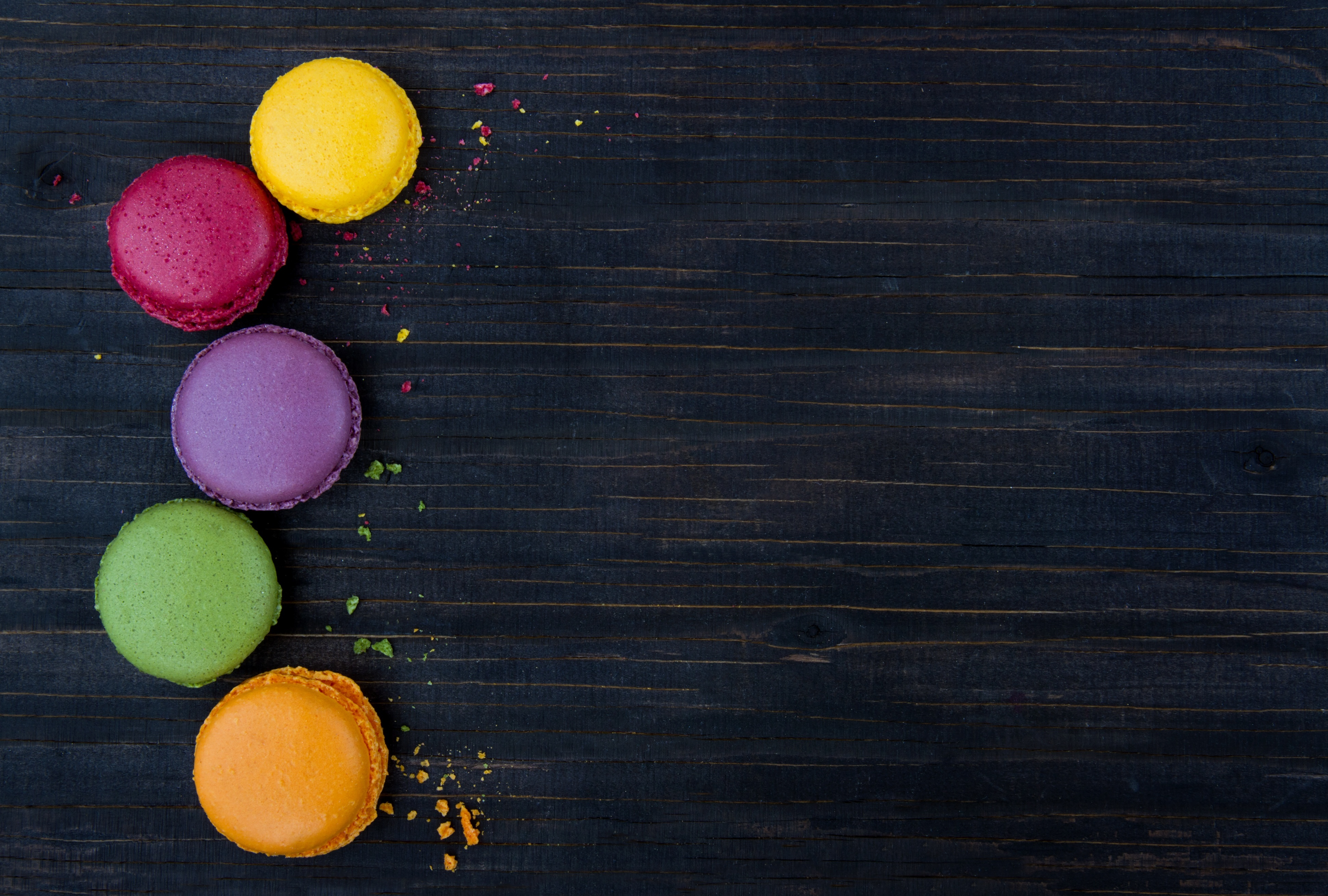 18837615 – macaroons background, colorful cookies on black wooden table